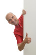 man peeking behind the blank poster