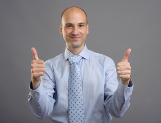 smiling businessman showing thumbs up sign