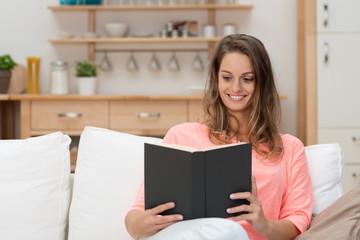 schöne junge frau liest ein buch in ihrer wohnung