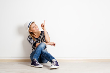 Beautiful woman pointing at copy space on empty wall