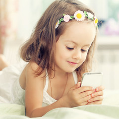 Little girl with mobile phone in her hands