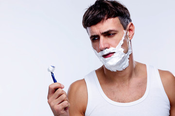 Portrait of a pensive man shaving over gray background
