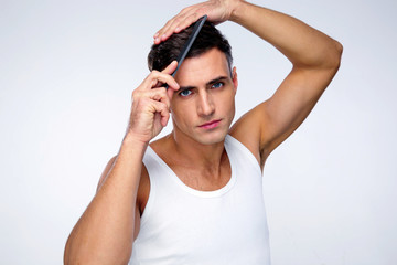 Serious man combing his hair over gray background