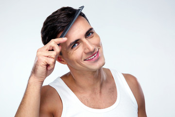 Happy man combing his hair over gray background