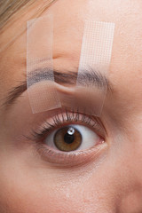 Close up of woman's eye taped open