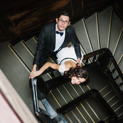 Young couple posing on staircase. Dark interior.