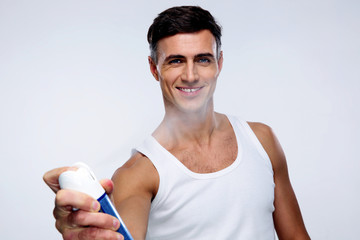 Happy man spraying deodorant over gray background