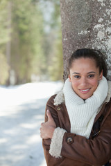 Smiling woman leaning against tree trunk in snow