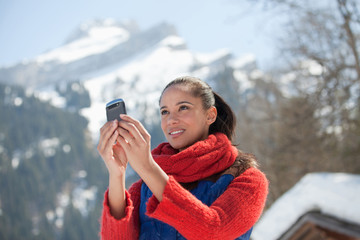 Woman checking cell phone with mountain in background