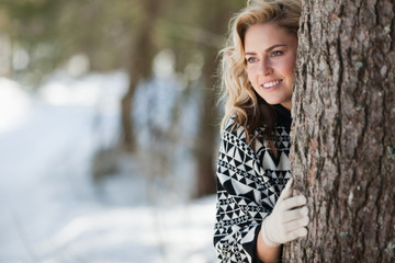 Woman peeking out from behind tree