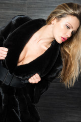 Fashion beautiful blonde woman posing in fur coat