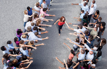 Woman walking between two groups of people, shaking hands