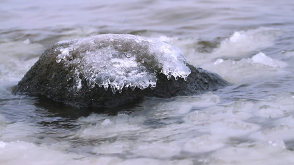 Frozen stone in winter cold sea
