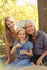 Three generations of women blowing bubbles