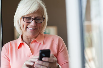 Smiling older woman using cell phone
