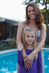 Mother and daughter standing by pool