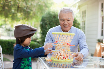 Older man and grandson playing outdoors