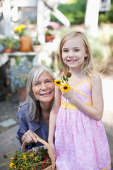 Older woman and granddaughter picking flowers