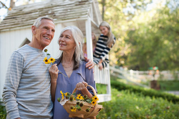 Older couple picking flowers outdoors