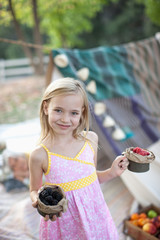 Girl holding cups of fruit outdoors