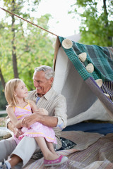 Older man and granddaughter relaxing outdoors