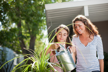 Mother and daughter watering plants outdoors