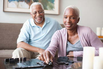 Laughing older couple playing dominoes