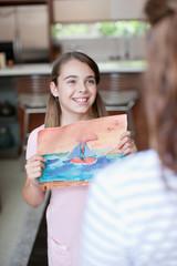 Girl showing mother artwork
