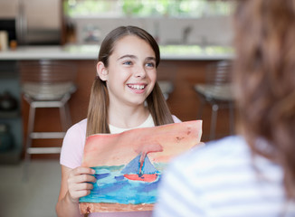 Girl showing mother artwork