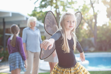 Girl wearing fairy wings in backyard