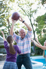 Older man playing basketball with granddaughters