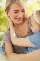 Smiling mother holding daughter outdoors