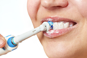 Woman brushing teeth electric toothbrush closeup isolated