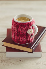 Knitted mug with tea on books