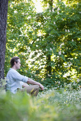 Man meditating in field of flowers