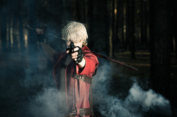 man with a sword and a gun in the hands of a smoky the forest