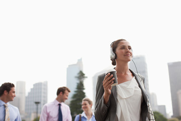 Businesswoman listening to headphones and carrying coffee