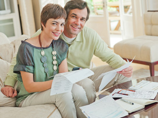 Couple on sofa paying bills