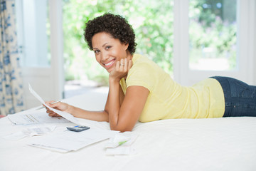 Woman laying on bed and paying bills