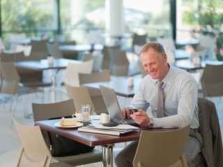 Businessman looking at cell phone in cafeteria