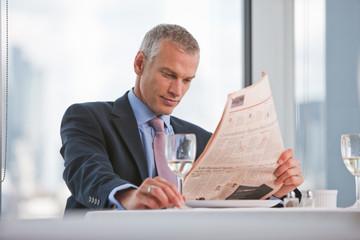 Businessman reading news paper in restaurant