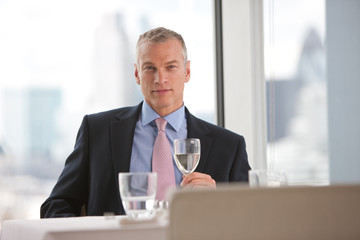 Businessman drinking white wine in restaurant