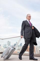 Businessman pulling luggage across urban balcony