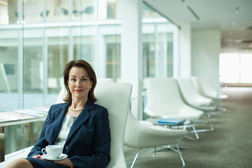 Businesswoman drinking coffee in waiting area