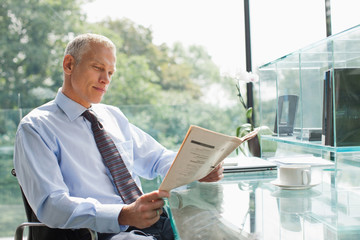 Businessman reading newspaper at desk