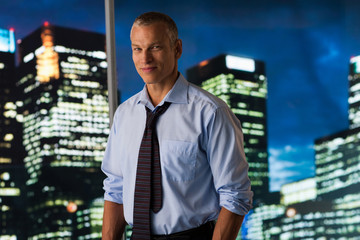 Serious businessman standing at glass wall with cityscape in background