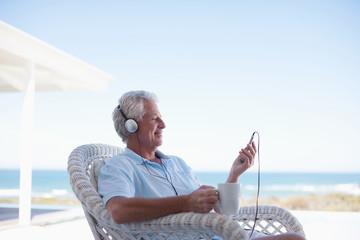 Senior man listening to mp3 player