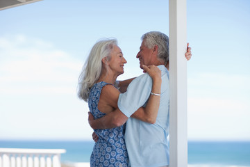 Senior couple hugging on patio and looking at ocean