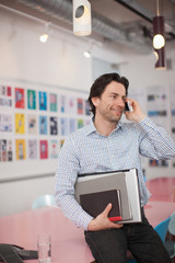 Smiling businessman holding laptop and books talking with cell phone  in office