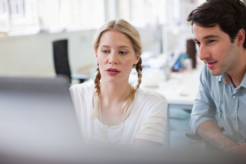Man and woman using laptop in office